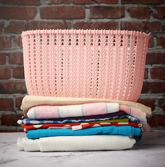 Stack of folded laundry and empty laundry basket