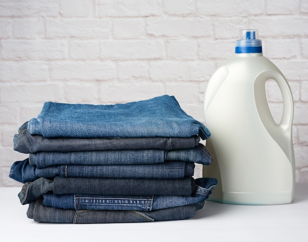 Stack of folded pairs of jeans and plastic detergent bottle