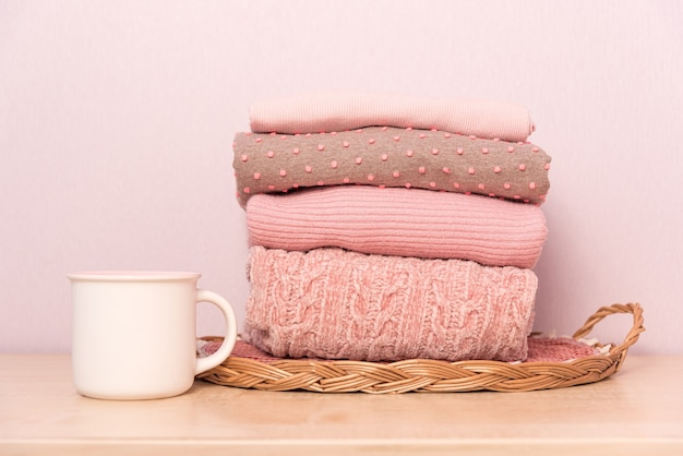 Stack of folded wool knitted sweaters in pink pastel colors on table with cup of tea