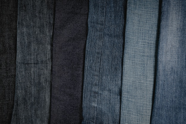 Stack of frayed jeans or blue jeans denim collection background