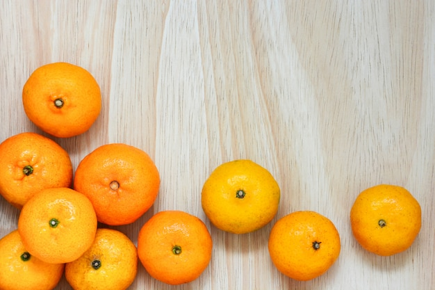 Stack of fresh mandarin oranges on wood