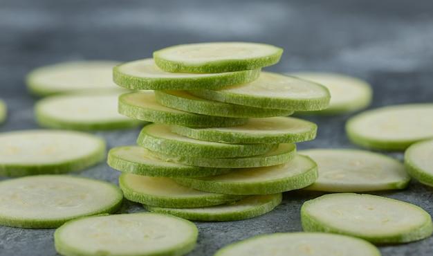 Pila di fette di zucchine fresche su sfondo grigio, foto ravvicinata.