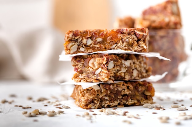Stack of fruit and nut bars, useful components, close up, for healthy concept. light background