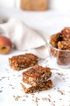 Stack of fruit and nut bars, useful components, for healthy concept. light background