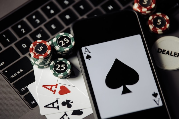 Stack of gambling chips, smartphone and playing cards on a laptop keaboard. close-up. online casino concept
