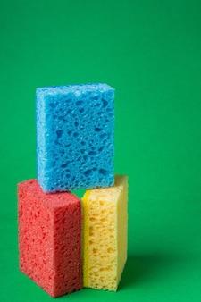 Стек геометрические блоки строительные абстрактные губки красного, желтого, синего цветов, на зеленой бумажной стене