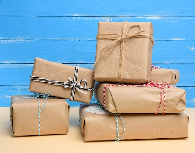 Stack of gifts wrapped in brown kraft paper and tied with rope, boxes on a blue background