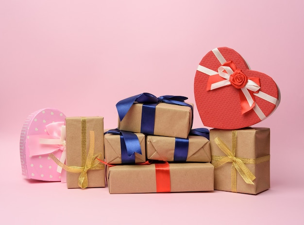 Stack of gifts wrapped in brown kraft paper and tied with silk ribbon, boxes on a pink background, copy space