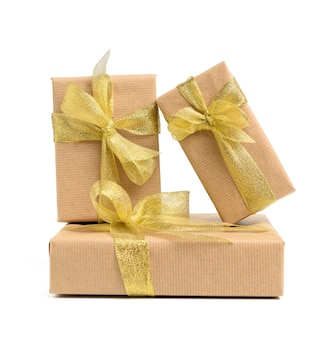 Stack of gifts wrapped in brown kraft paper and tied with silk ribbon