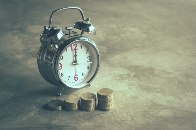 Stack of gold coins with alarm clock on cement floor