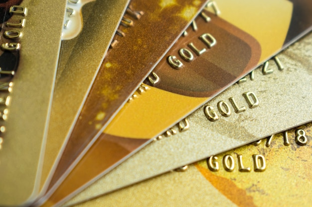 Stack of gold credit cards on dark background