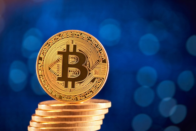 Stack of golden bitcoins with one bitcoin on its edge placed on blurred blue background.