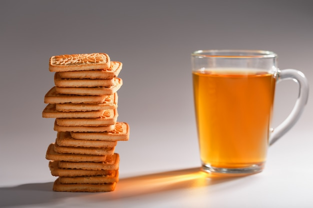 A stack of golden wheat cookies and a mug of fragrant green tea on gray