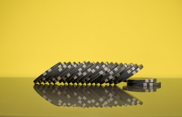 Stack of gray casino chips on golden background