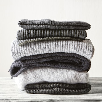 Stack of gray woolen knitted sweaters on a white surface