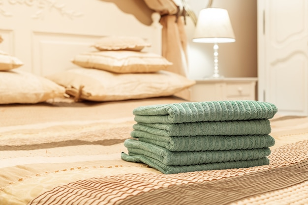 Stack of green hotel towel on bed in bedroom interior
