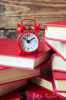 A stack of hardcover books and an alarm clock on a wooden table. copy space for text