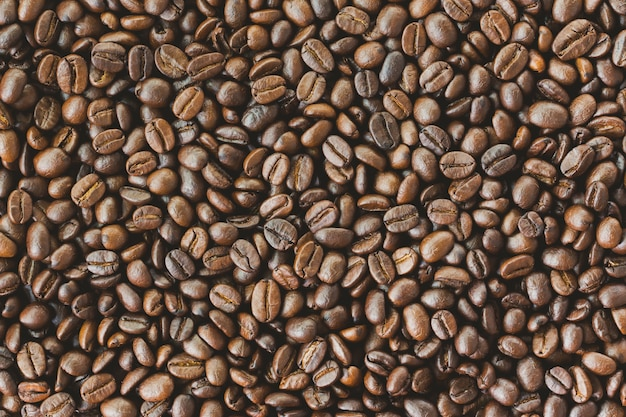 Stack or heap of roast coffee beans in top view flat lay in close up view