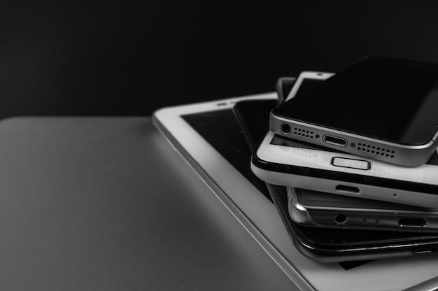 Stack of high-end smartphones on black desk.