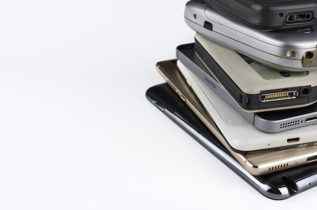 Stack of high-end smartphones on white desk.