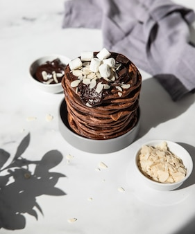 Stack of homemade chocolate pancakes with melted chocolate ground almond and marshmallow direct sunlight and hard shadows