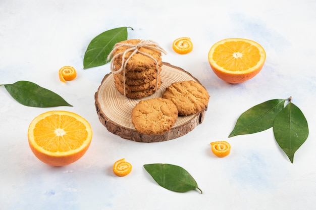Stack of homemade cookie on wooden board and half cut orange with leaves over white surface.