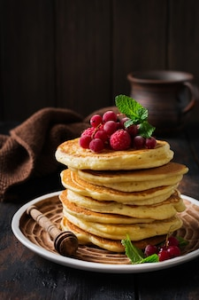 Stack of homemade little pancakes with honey, fresh raspberries and red currants on an old wooden surface