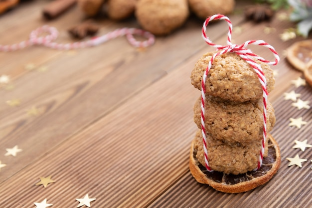 Stack of homemade oatmeal cookies. christmas healthy cookies, biscuits. rustic wooden table. winter decoration.