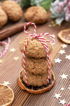 Stack of homemade oatmeal cookies, christmas healthy cookies, biscuits, rustic wooden table.