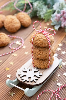 Stack of homemade oatmeal cookies on sleigh. christmas healthy cookies, biscuits. rustic wooden table. winter decoration.
