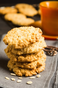 Stack of homemade oatmeal cookies on tissue with cup of tea or coffee