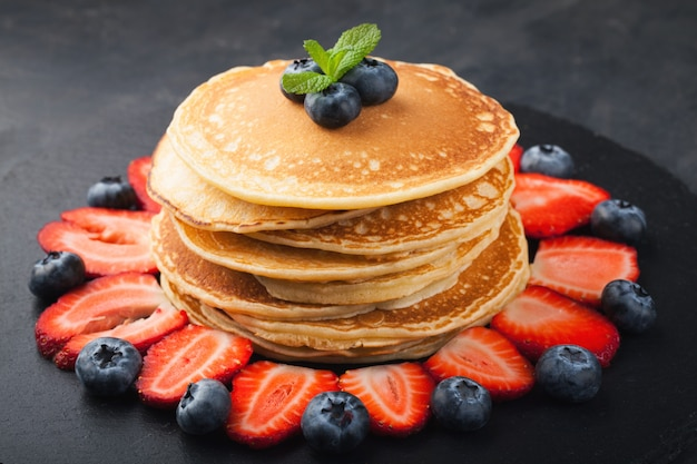 A stack of homemade pancakes with fresh berries.