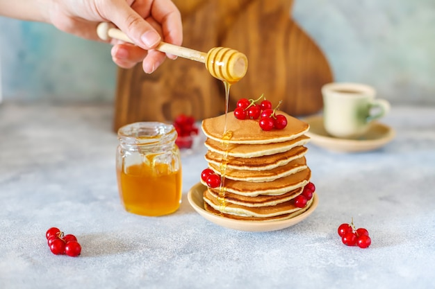 Stack of homemade pancakes with honey syrup and berries