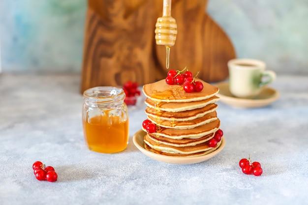 Pila di pancake fatti in casa con sciroppo di miele e frutti di bosco