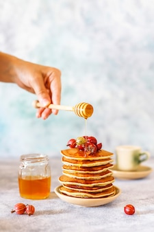 Stack of homemade pancakes with honey syrup and berries.