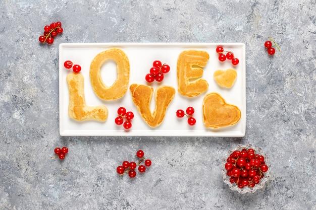 Pila di pancake fatti in casa con sciroppo di miele e frutti di bosco.