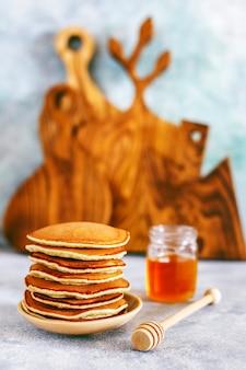 Pila di frittelle fatte in casa con sciroppo di miele e frutti di bosco.