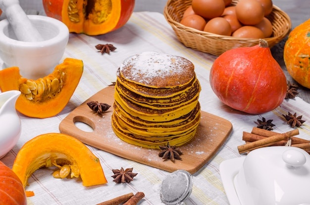 Stack of homemade pumpkin punkcakes with powdered sugar on top on a light background.