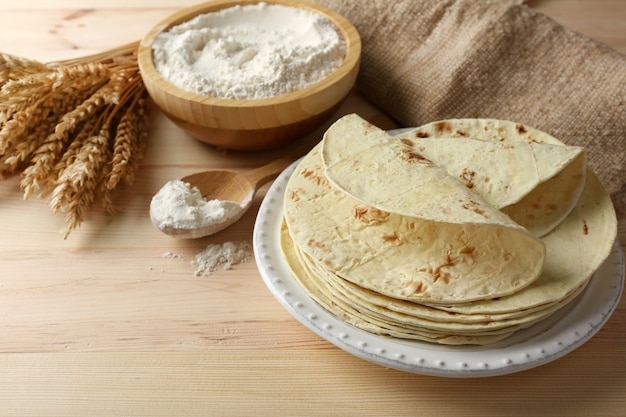 Stack of homemade whole wheat flour tortilla on plate, on wooden table