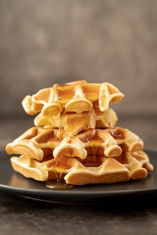 Stack of honey covered waffles on plate with copy space