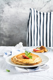 Stack of hot crepes over kitchen table