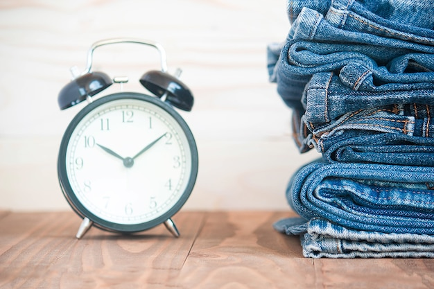 Stack of jeans and classic timepieces on old wooden
