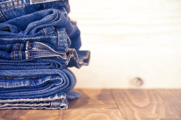 Stack of jeans on old wood flooring, fashion concept