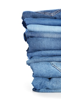 Stack of jeans pants on white