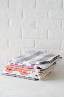 Stack of kitchen towels or napkins in interior of white kitchen.
