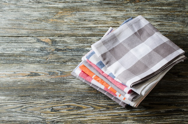 Stack of kitchen towels or napkins over the rustic wooden table.
