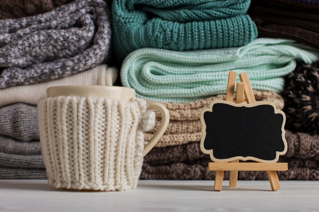 A stack of knitted clothes of different colors and textures, on the table next to a cup in a case