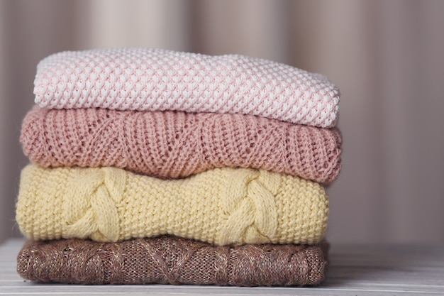 Stack of knitted clothes on wooden table indoors