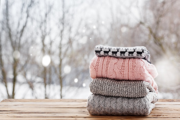 Stack of knitted clothes on wooden table on winter nature ourdoor