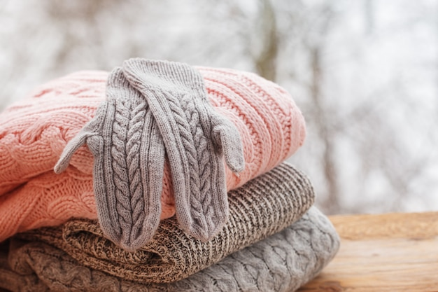 Stack of knitted clothes on wooden table on winter nature outdoor.